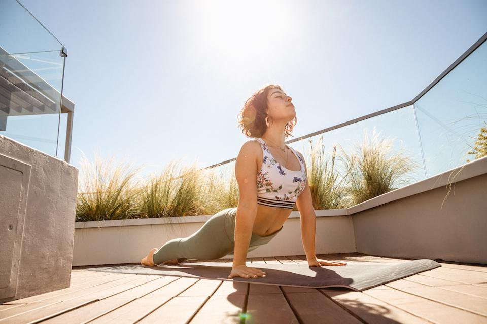 a young woman in an upward dog yoga position on a deck during the day
