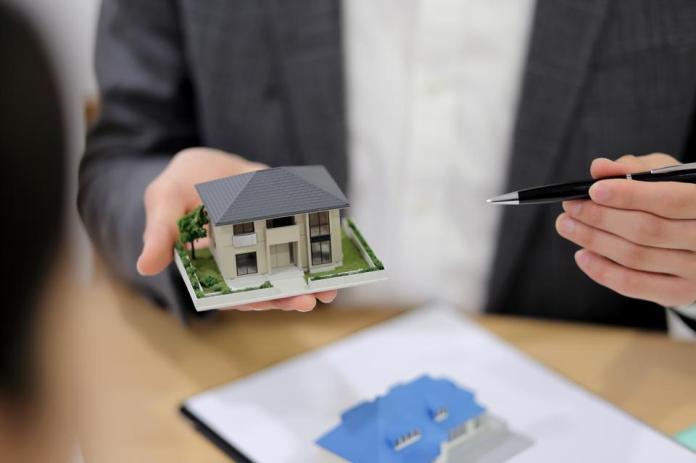 Businessman holding model house