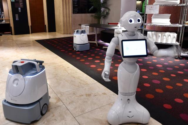 Humanoid and cleaning robot ready to greet guests in lobby of coronavirus hotel in Tokyo.