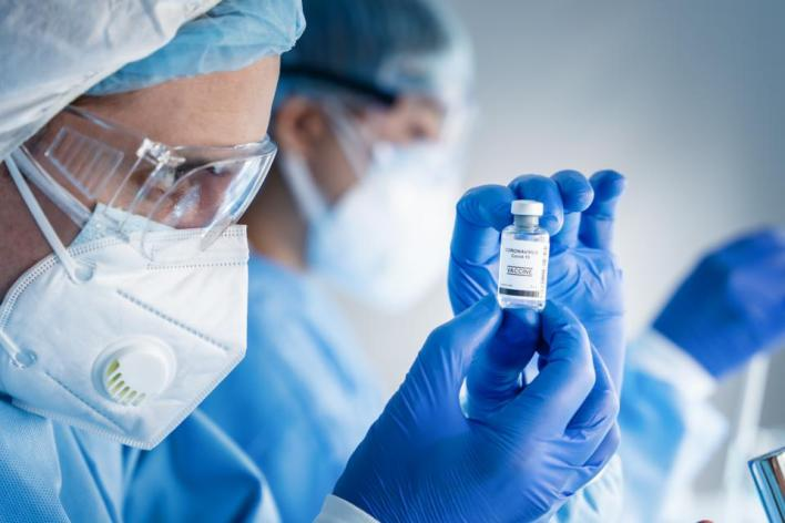 coronavirus covid-19 vaccine bottle in hands of pharmacuetical and vaccine research scientist in laboratory, coronavirus covid-19 vaccine development