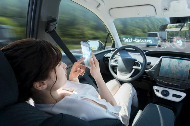 woman using smart phone in autonomous car. self driving vehicle. autopilot. automotive technology.