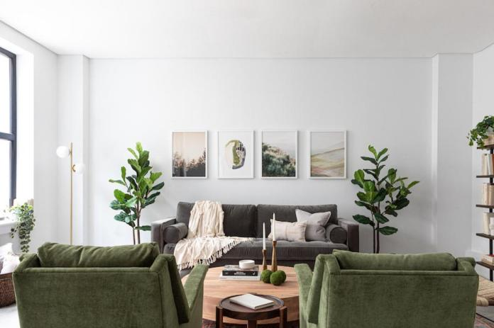 A living room at Common Frankford with green chairs and a grey sofa.