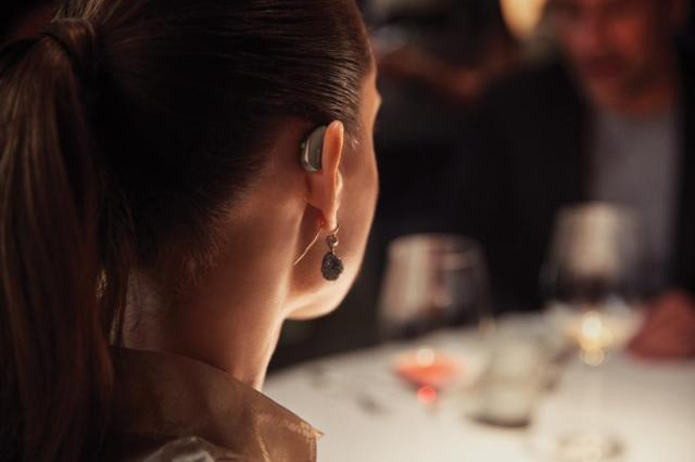 Woman wearing a tiny hearing aid behind her ear