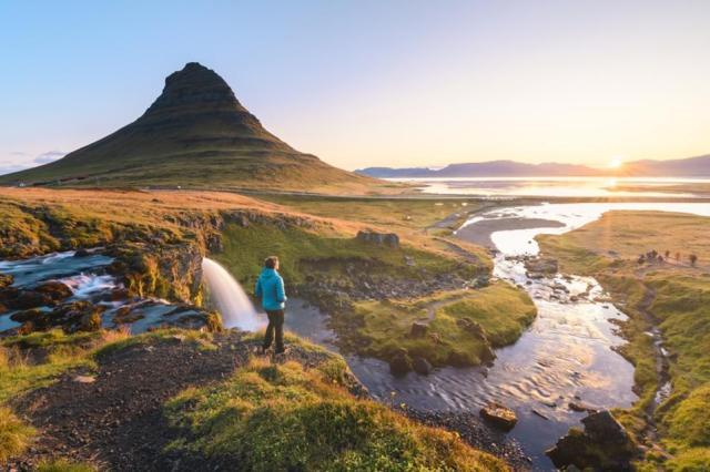 Man admiring the sunrise at mount Kirkjufell, Iceland