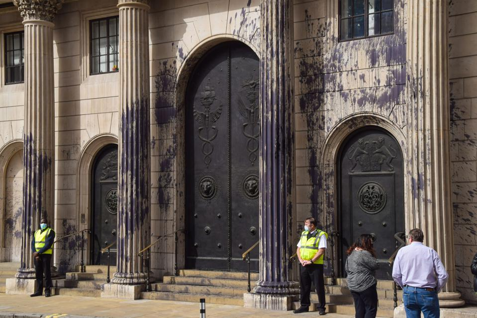 People stand outside the Bank of England covered in fake oil...