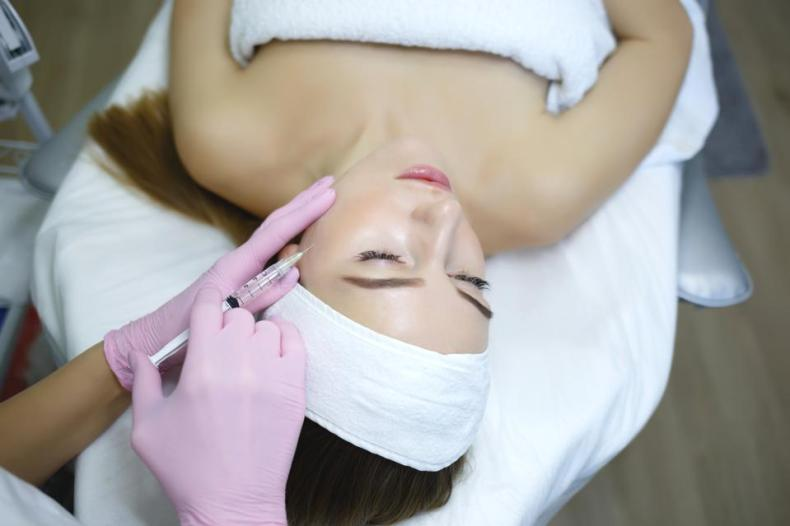 Cosmetologist does injections anti wrinkle of a beautiful woman. Women's cosmetology in the beauty salon.