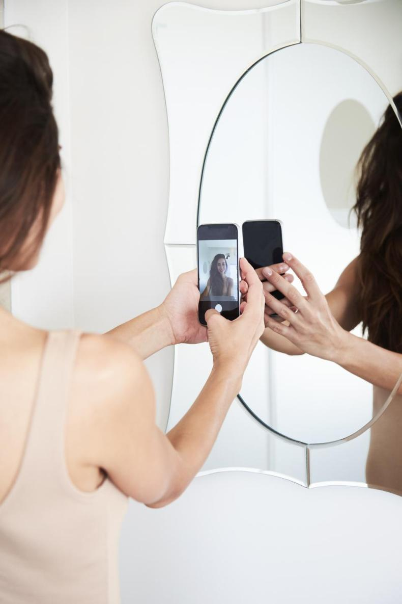 Woman takes selfie in the mirror.