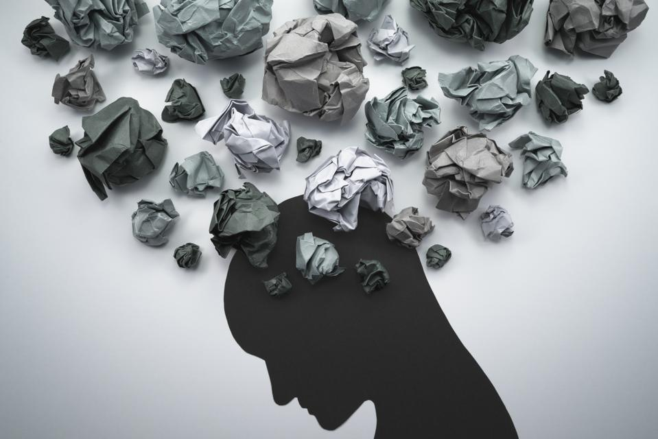 Silhouette of troubled person head, with waste paper bundles to represent thoughts