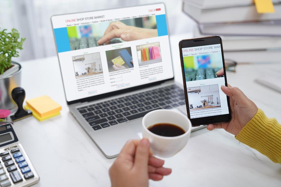 Hands holding a phone a phone and a coffee cup with a laptop screen open in front showing an online shop