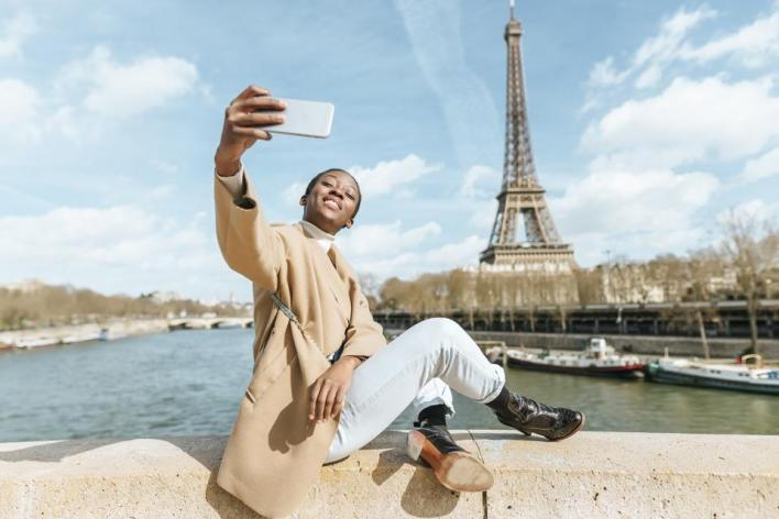 France, Paris, Woman sitting on bridge over the river Seine with the Eiffel tower in the background taking a selfie