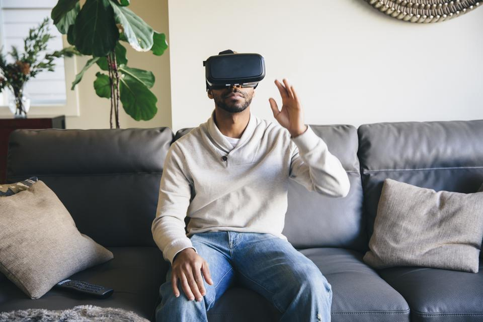 Hombre de raza mixta que usa gafas de realidad virtual