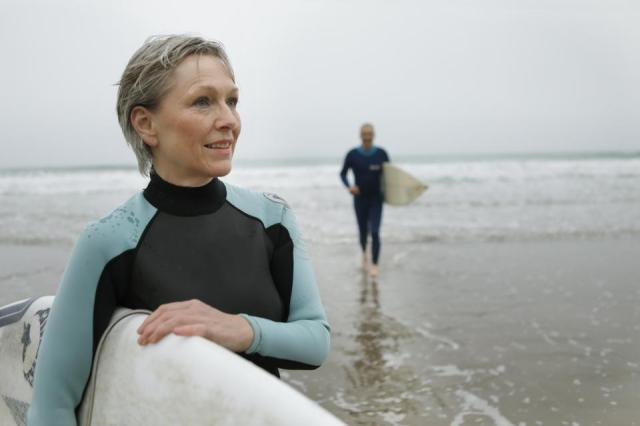 Older couple on beach with surfboards