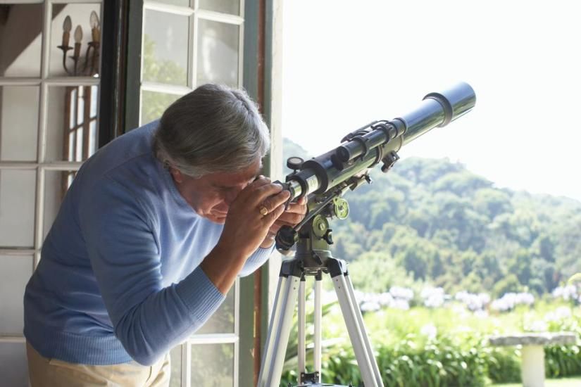 Senior man using the telescope at home