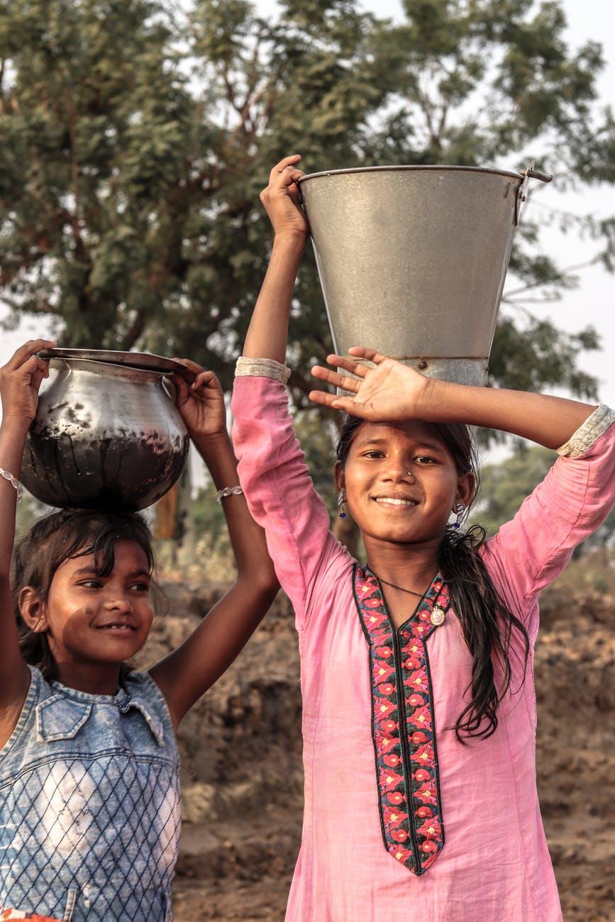 two asian girls carrying a bucket