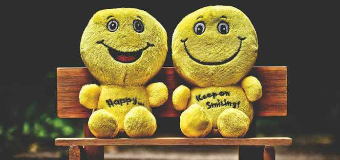 Two emoji stuffed dolls on a bench.