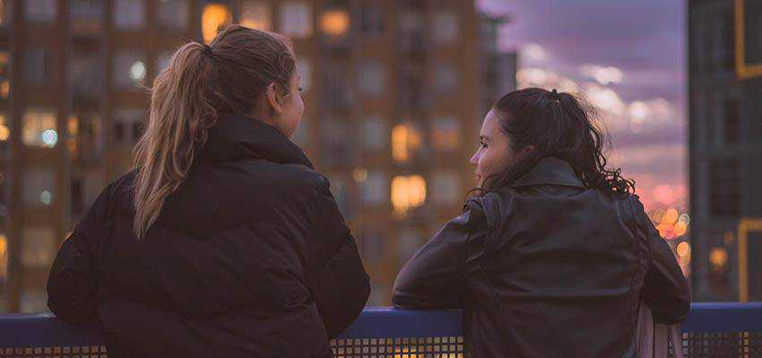 Two women outside, overlooking a city.