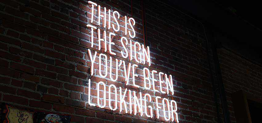 """A neon sign that reads """"This is the sign you've been waiting for""""."""