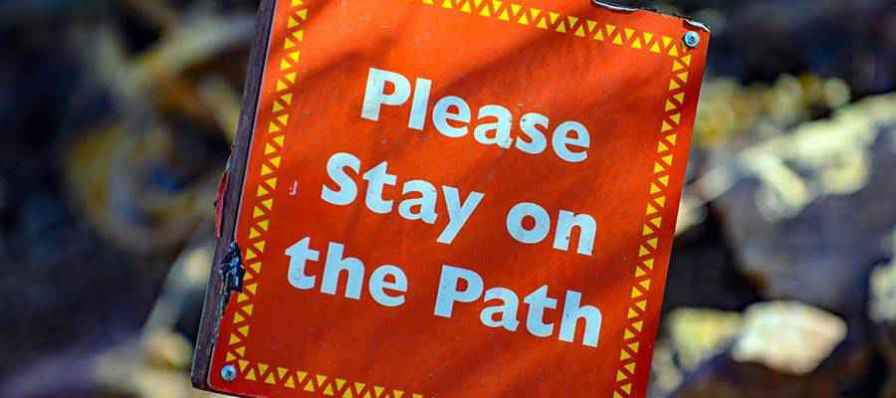 "A sign that reads ""Please stay on the path""."