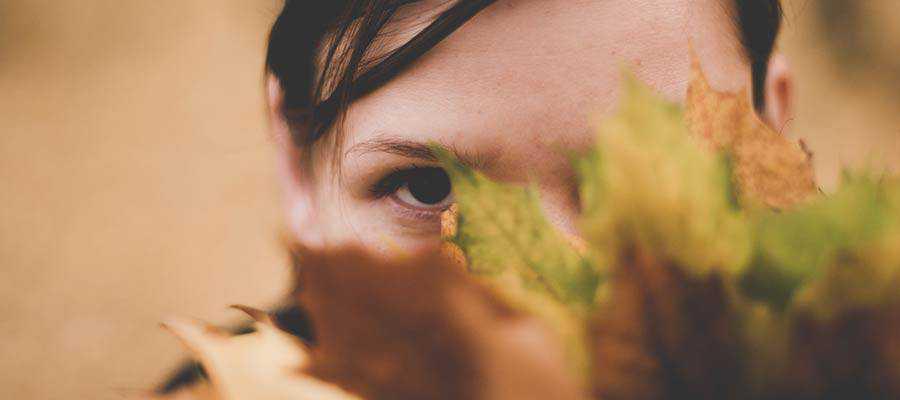 A person hiding behind a plant.