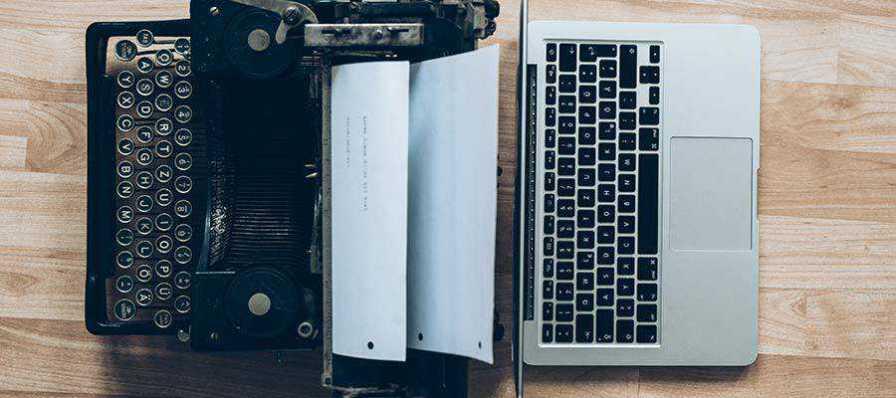 A typewriter sits next to a laptop computer.