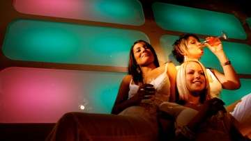 Group of individuals, to illustrate article on autistic V NT communication. Oh, to feel this NT! Confidently wearing white, casually drinking in a happpy group and enjoying some garish lighting...