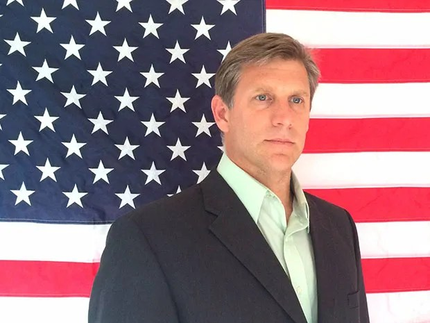 A photo of Transhumanist Party presidential candidate Zoltan Istvan standing in front of an American flag.
