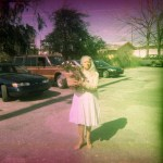Woman standing in the street. The film has light leaks.