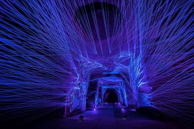 Blue strings of light in a darkened room