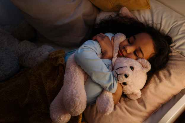 an adorable girl hugging her teddy bear while sleeping