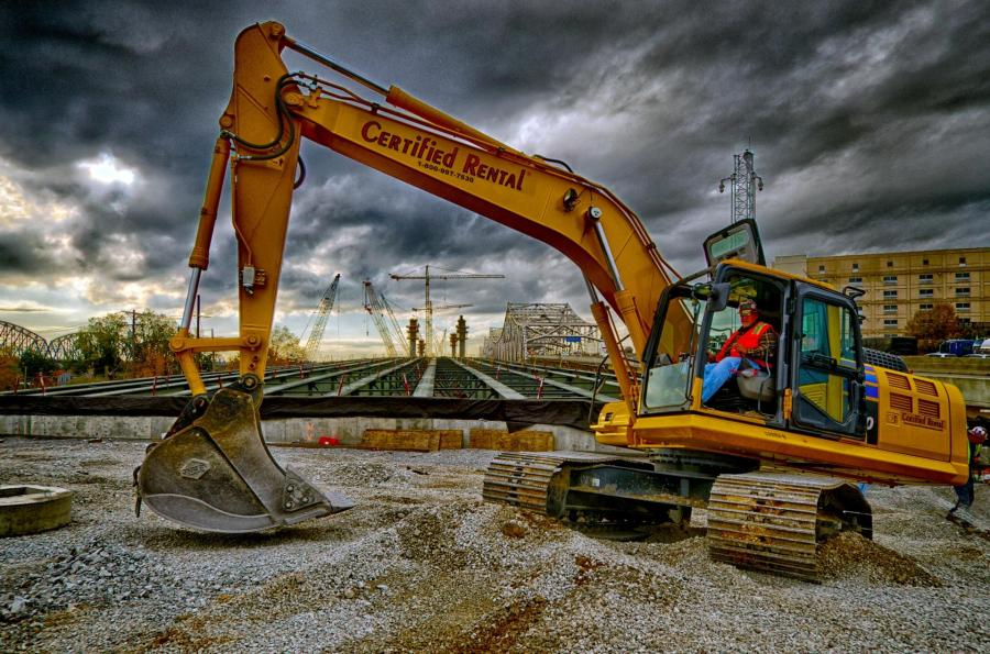 In this scene from the Indiana Approach Brian Kirker operates an excavator as they install drainage pipes for the new bridge. In the background the towers for the Downtown  Span can be seen along with the girders that will connect the bridge to I-65 North in Indiana.