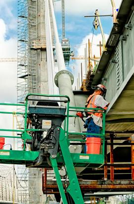 Two ironworkers drilling the holes to connect the side girder in place. #3