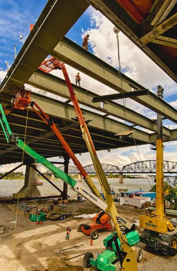 Two ironworkers are drilling the holes to connect the side girder in place while two other Ironworkers walk on the beams above them. #2