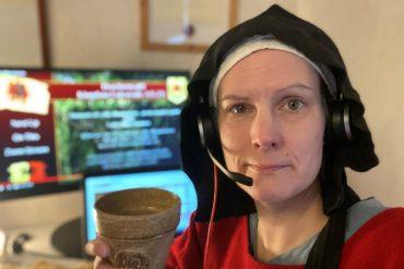 En medelålders kvinna i medeltidskläder och headset sitter framför två datorskärmar. Hon tittar in i kameran och håller upp ett krus.