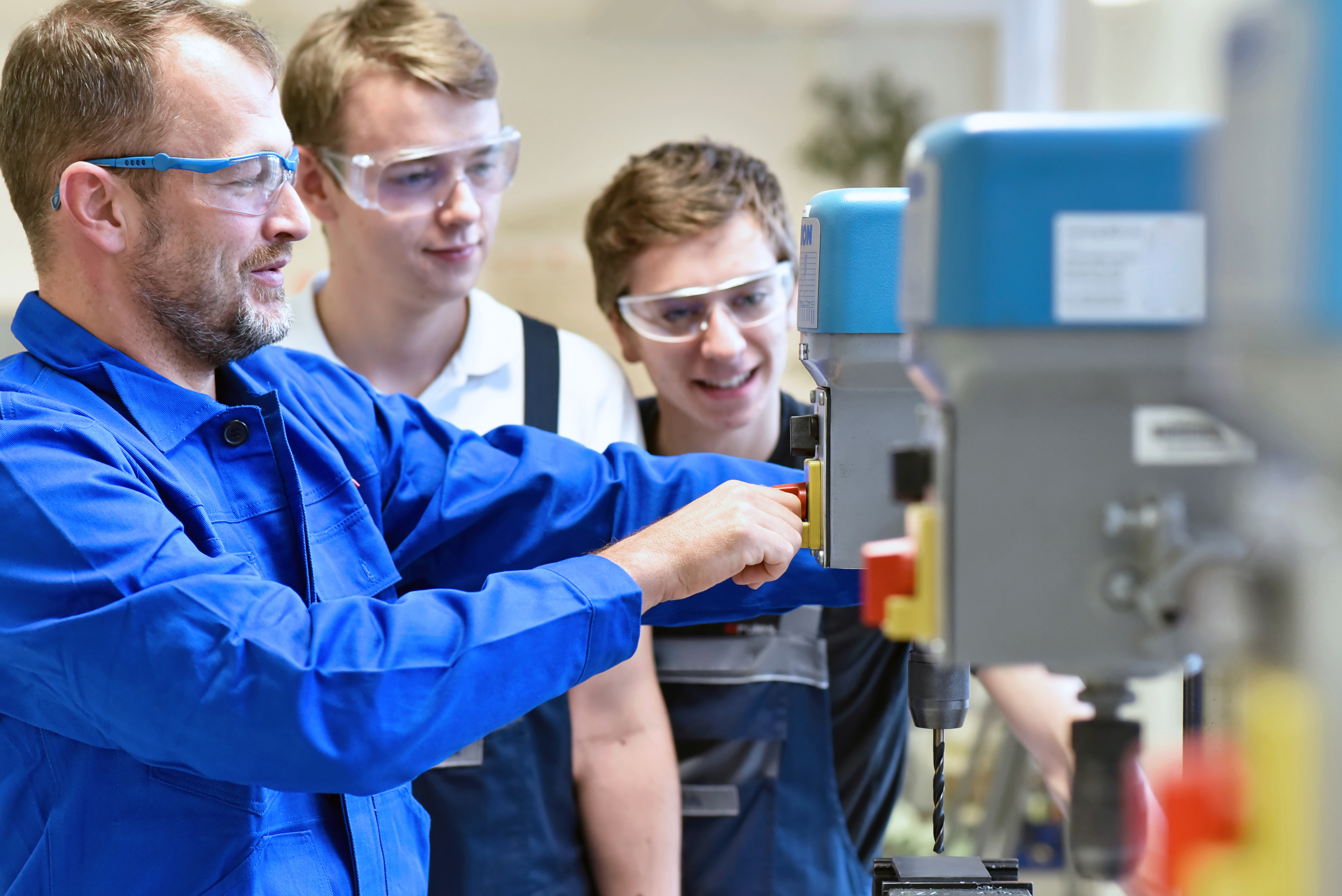 Group of young people in mechanical vocational training with teacher at drilling machine