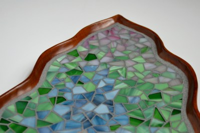 close-up of stained glass mosaic on wooden leaf plate