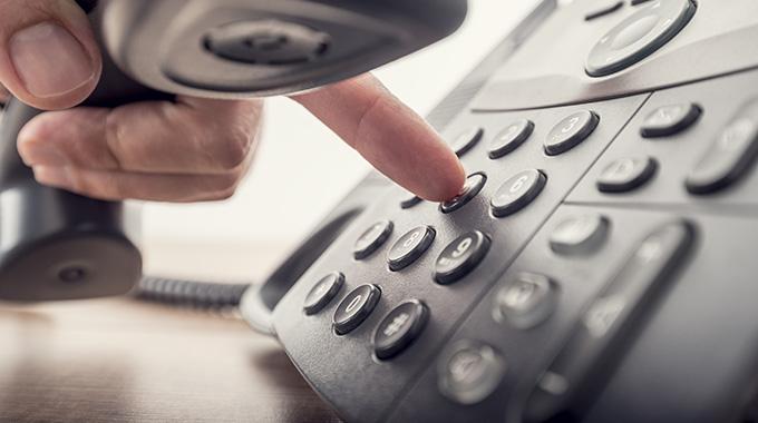 Male hand dialing on-premise voip phone - Speros - Savannah, GA