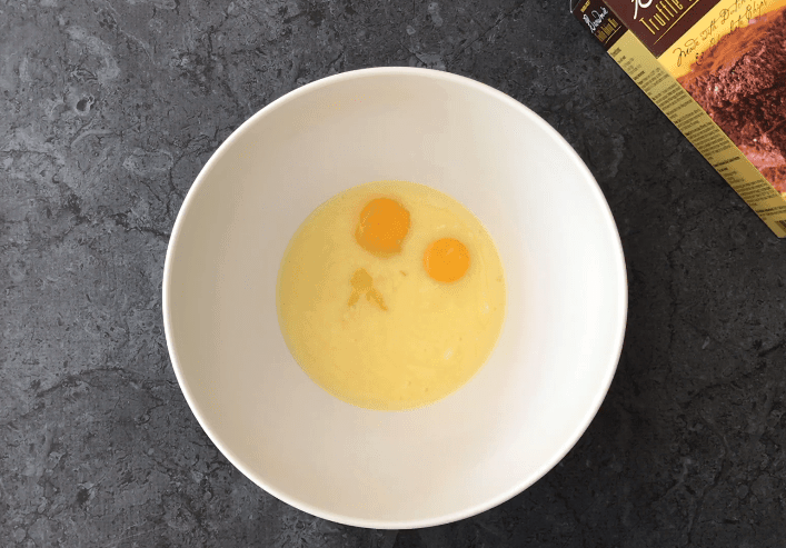 Adding eggs to the melted butter in a bowl.