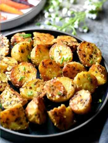 Perfectly roasted potatoes served on a black plate.