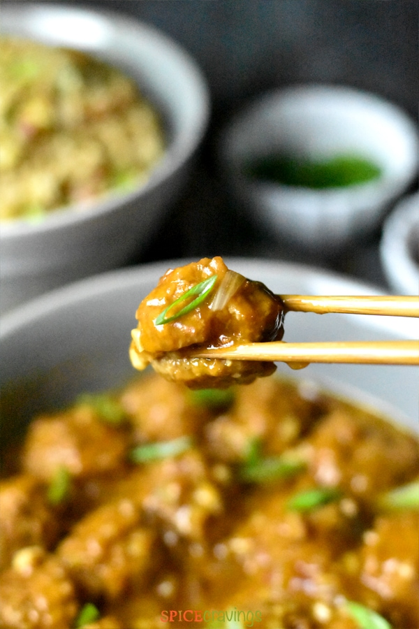 Vegetable manchurian meatball between two chopsticks