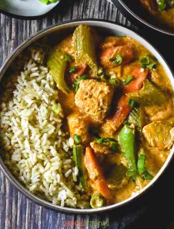 Thai red curry served with brown rice in a brown bowl on a wooden backdrop