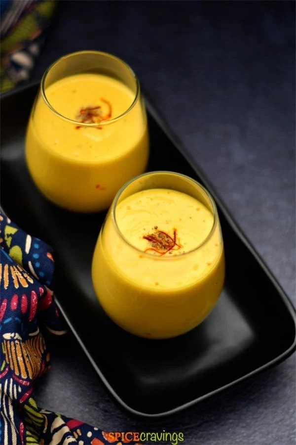Two glasses of mango lassi placed on a black plate