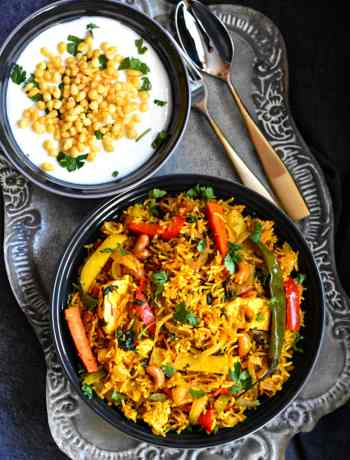 Bowl of Indian spiced vegetable biryani with a side of yogurt