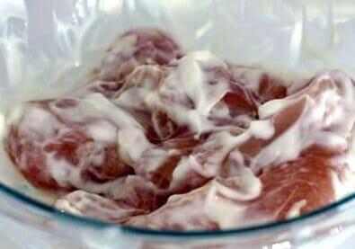 recipe for chciekn rezala. Chicken marinated with yoghurt in a bowl