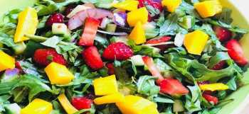 A bowl of Strawberry summer salad with fresh strawberries, arugula leaves, mango and mango chutney dressing