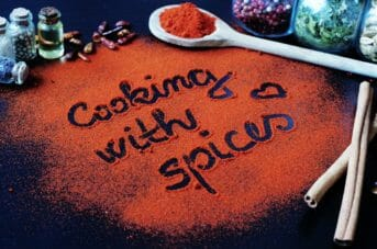 Cooking with spices written with red chilli and spice jars