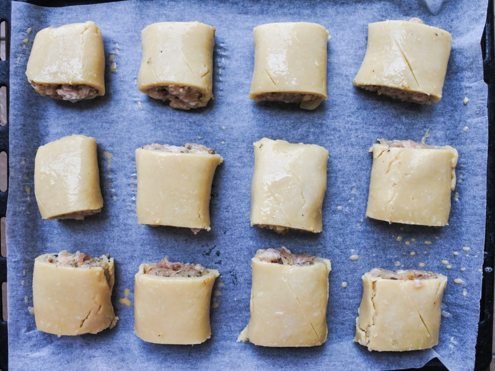 cut up sausage rolls on a baking tray before baking