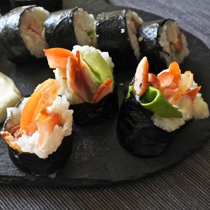 BLT sushi rolls on black slate