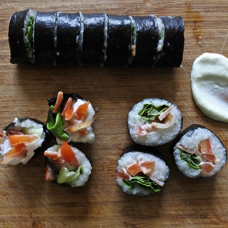 cut up BLT sushi rolls on a wooden cutting board