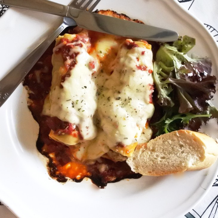 Cannelloni with spicy chorizo sauce served with bread and salad