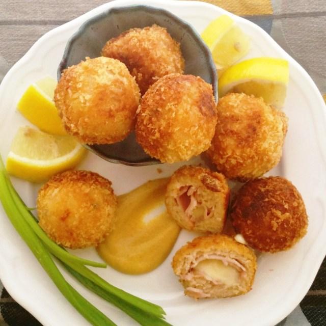 Chicken Cordon Bleu bites on a plate with mustard, lemon and scallion